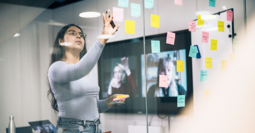 Woman places sticky notes in work meeting