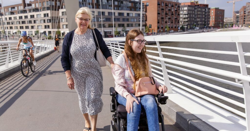 A woman and a wheelchair with a woman accompanying her on a Helsinki bridge.