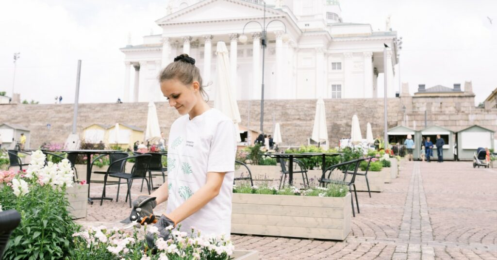 Woman watering flowers in Senate Square